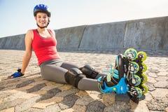 Skater louro desportivo de sorriso que senta-se na terra fotografia de stock royalty free