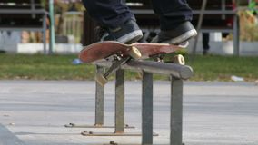 Skater make grind feeble 180 on rail in skatepark, close-up view in slowmotion. Detailed angle. Skater make grind trick feeble 180 out - also feeble to fakie stock footage
