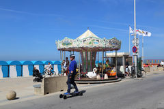 Skater at Malo les Bains beach in Dunkirk, France. Dunkirk, France - May 31, 2017: Man on skateboard and tourists at a merry-go-round carousel on the promenade Stock Photo