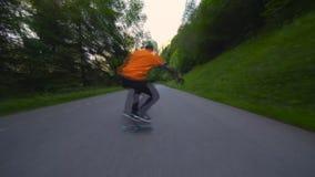 Skater masculino profesional joven que realiza los trucos que patinan cuesta abajo en el camino peligroso del paisaje de la monta almacen de video