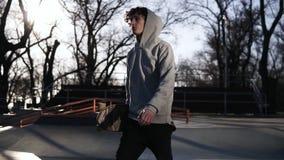 Skater novo em caminhadas cinzentas do hoodie em um parque do patim com um skate nas mãos Sideview Movimento lento filme