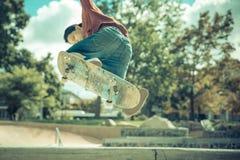 Skater novo que pratica no parque do patim fotografia de stock