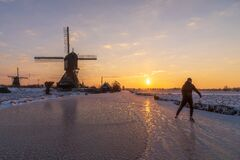 Free Skater On The Frozen Canal Along The Windmills Alignment Stock Image - 215086351
