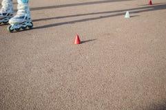 Skater practicing slalom. Roller skater practicing slalom along a line of cones on asphalt Stock Photo