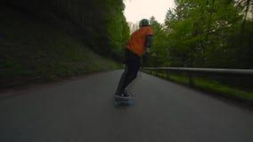 Skater profesional masculino joven que realiza los trucos que patinan cuesta abajo en el camino peligroso del paisaje de la monta almacen de video