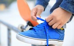 Skater que amarra o laço no parque do patim fotografia de stock royalty free