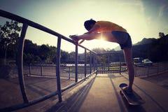 Skater que estira las piernas foto de archivo