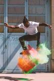 Skater que faz o kickflip com pó colorido do holi fotos de stock