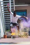 Skater que hace el kickflip con el polvo colorido del holi Fotos de archivo