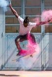 Skater que hace el kickflip con el polvo colorido del holi Fotografía de archivo libre de regalías