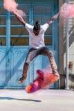 Skater que hace el kickflip con el polvo colorido del holi Imagen de archivo libre de regalías