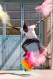 Skater que hace el kickflip con el polvo colorido del holi Imágenes de archivo libres de regalías