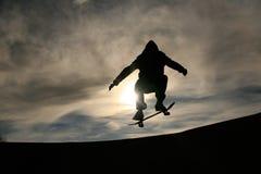 Skater que hace el ollie en puesta del sol Foto de archivo
