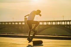 Skater que hace un truco del ollie con el brillo del sol brillante en fondo foto de archivo