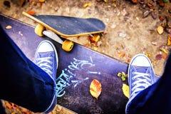 Skater que se coloca en un banco en parque de la ciudad Imagen de archivo libre de regalías