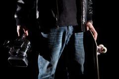 Skater que sostiene una cámara de vídeo y un monopatín Foto de archivo