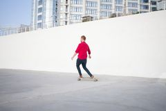 Young skater riding in the summer. Skater in red shirt and blue jeans riding near beach on longboard during sunrise, sea or ocean background stock photos