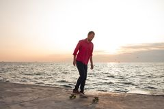 Young skater riding in the summer. Skater in red shirt and blue jeans riding near beach on longboard during sunrise, sea or ocean background royalty free stock image