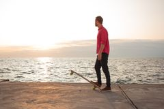 Young skater riding in the summer. Skater in red shirt and blue jeans riding near beach on longboard during sunrise, sea or ocean background royalty free stock photos