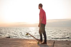 Young skater riding in the summer. Skater in red shirt and blue jeans riding near beach on longboard during sunrise, sea or ocean background royalty free stock images