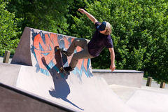Skater Riding a Skate Ramp. Action shot of a skateboarder skating on a concrete skateboarding ramp at the skate park. Shallow depth of field Royalty Free Stock Image