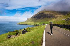 Skater riding a skateboard through the village of Bour on the Faroe Islands