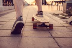 Skater`s legs on Longboard. Close-up image of a skater`s legs on longboards royalty free stock photography