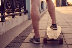 Skater`s legs on Longboard. Close-up image of a skater`s legs on longboards stock photos