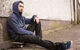 Skater sitting on his board looking thoughtful. Skater with hood up sitting on his board looking thoughtful outside the skate park Royalty Free Stock Image