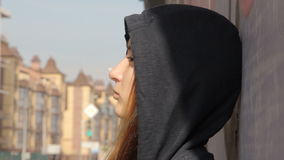 Skater style teenager girl in a hoody with the hood on and loose multicolored hair against the graffiti looking into the stock video