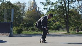 Skater in a suit goes the trick FS Pop Shove-it skate park stock video footage
