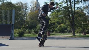 Skater in a suit goes the trick Shove-it skate park stock footage