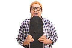 Skater superior alegre que guarda um skate imagem de stock