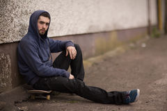 Skater taking a break outside the skate park and looking at camera Stock Image