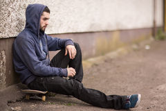 Skater taking a break outside the skate park Stock Photo