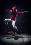 Skater trick. Skateboarder doing trick with grunge background red hoodie and skill Royalty Free Stock Image