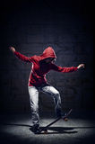 Skater trick. Skateboarder doing trick with grunge background red hoodie and skill stock image