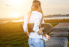 Skater young woman on sunset. Woman with Royalty Free Stock Photography
