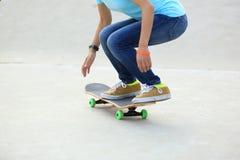 Skateres de la mujer que montan en un monopatín fotos de archivo