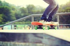 Skateres de la mujer que saltan en un monopatín fotografía de archivo