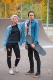 Skateres jovenes del individuo y de la muchacha, al aire libre en un día brillante del otoño Fotos de archivo libres de regalías