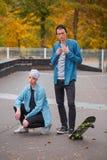 Skateres jovenes del individuo y de la muchacha, al aire libre en un día brillante del otoño Imagen de archivo