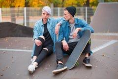 Skateres jovenes del individuo y de la muchacha, al aire libre en un día brillante del otoño Foto de archivo libre de regalías