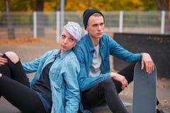 Skateres jovenes del individuo y de la muchacha, al aire libre en un día brillante del otoño Fotos de archivo
