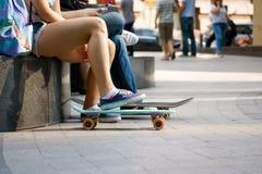 Skateres jovenes que descansan en parque el día de verano Fotografía de archivo