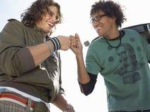 Skateres masculinos alegres que dan un topetón del puño Imagen de archivo