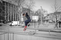 Skateres que moem uma barra em um parque do patim Foto de Stock