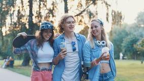 Skateres sonrientes jovenes en el parque Imágenes de archivo libres de regalías