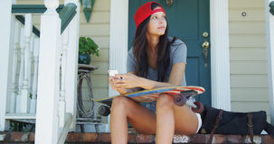 Skatergirl sitting on porch texting Royalty Free Stock Image