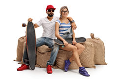 Skaters with a longboard and a skateboard sitting on burlap sack Stock Image